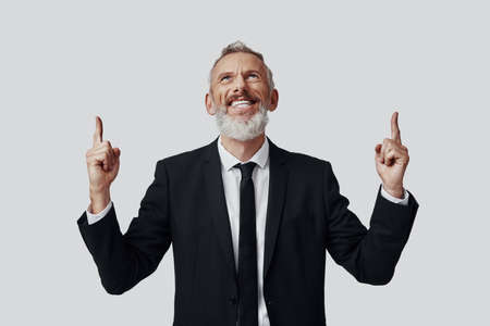 Happy mature man in full suit pointing copy space and smiling while standing against grey background