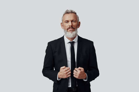 Elegant mature man in full suit adjusting jacket and looking at camera while standing against grey background Imagens