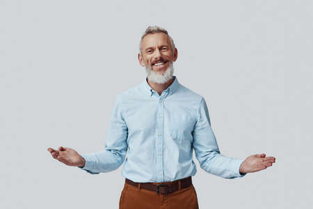 Happy mature man looking at camera and keeping arms outstretched while standing against grey background