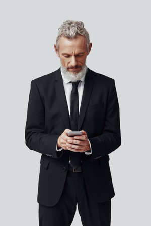 Thoughtful mature man in full suit using smart phone while standing against grey background Imagens