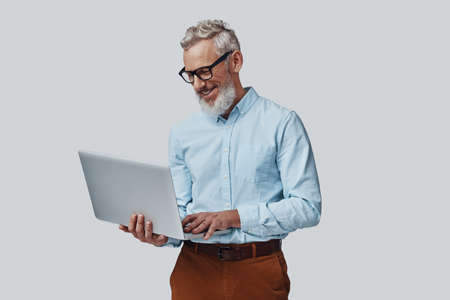 Happy mature man smiling and working using laptop while standing against grey background