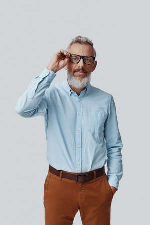 Confident mature man looking at camera and adjusting eyewear while standing against grey background Imagens