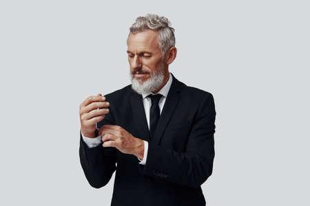 Elegant mature man in full suit adjusting sleeve while standing against grey background Imagens