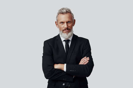 Confident mature man in full suit looking at camera and keeping arms crossed while standing against grey background