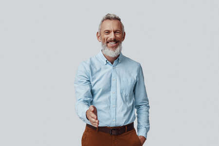 Happy mature man looking at camera and greeting you while standing against grey background