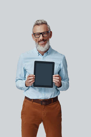 Confident mature man looking at camera and pointing copy space on digital tablet while standing against grey background
