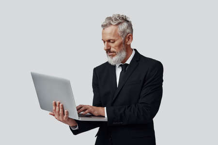 Confident mature man in full suit working using laptop while standing against grey background