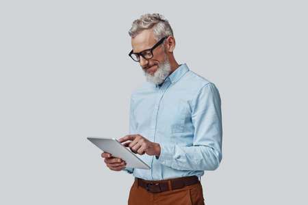 Thoughtful mature man working using digital tablet and smiling while standing against grey background