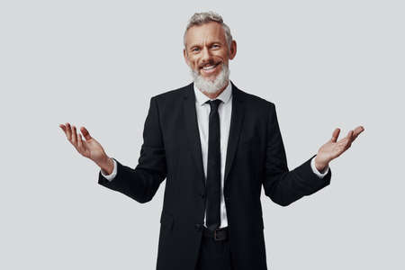 Confident mature man in full suit keeping arms outstretched and looking at camera while standing against grey background