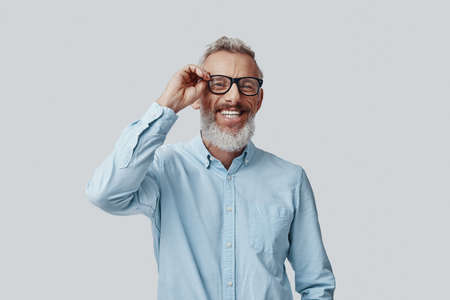 Happy mature man looking at camera and adjusting eyewear while standing against grey background Imagens