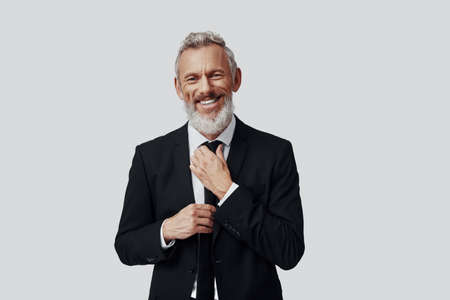 Elegant mature man in full suit adjusting tie and looking at camera while standing against grey background