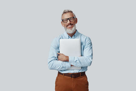 Happy mature man smiling and carrying laptop while standing against grey background Imagens