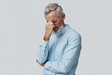Tired mature man suffering from headache while standing against grey background Imagens