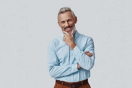Happy mature man looking at camera and keeping hand on chin while standing against grey background Imagens