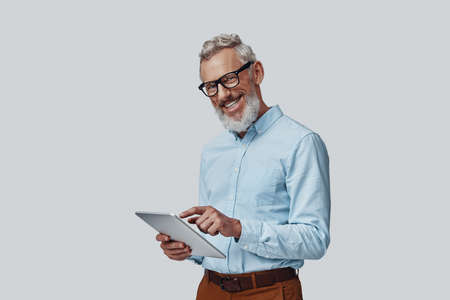 Happy mature man working using digital tablet and smiling while standing against grey background Imagens