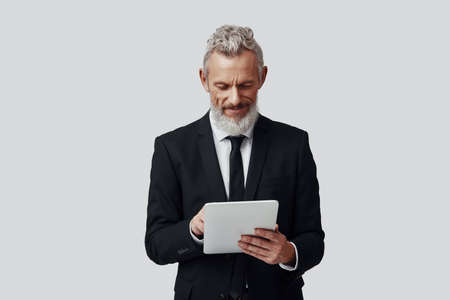 Confident mature man in full suit working using digital tablet and smiling while standing against grey background Imagens