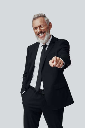 Confident mature man in full suit pointing you and looking at camera while standing against grey background