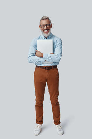 Full length of happy mature man smiling and carrying laptop while standing against grey background Imagens