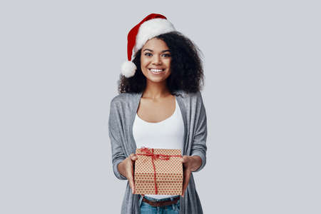 Beautiful young African woman in Santa hat giving you Christmas present and smiling while standing against grey background