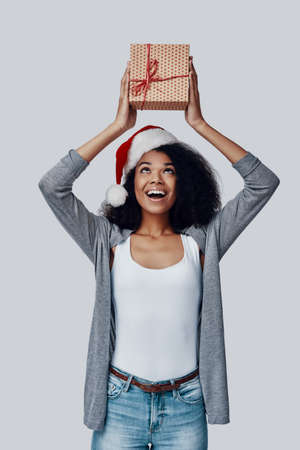 Happy young African woman in Santa hat holding Christmas present and smiling while standing against grey background