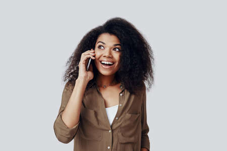 Beautiful young African woman talking on the smart phone and smiling while standing against grey background