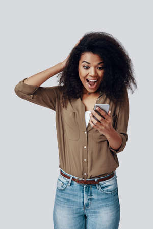 Shocked young African woman using smart phone and smiling while standing against grey background Reklamní fotografie