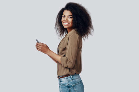 Beautiful young African woman using smart phone and smiling while standing against grey background 版權商用圖片