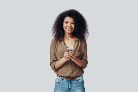Happy young African woman using smart phone and smiling while standing against grey background