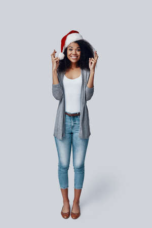Full length of playful young African woman in Santa hat keeping fingers crossed and smiling while standing against grey background