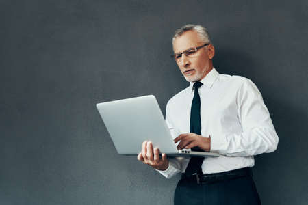 Handsome senior man in elegant shirt and tie using laptop while standing against grey background