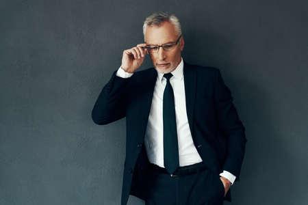 Handsome senior man in full suit adjusting eyewear while standing against grey background Reklamní fotografie