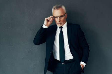 Handsome senior man in full suit adjusting eyewear while standing against grey background 免版税图像