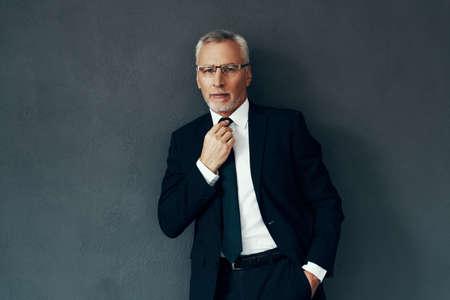 Hombre mayor guapo en traje completo mirando a la cámara y ajustando la corbata mientras está de pie contra el fondo gris