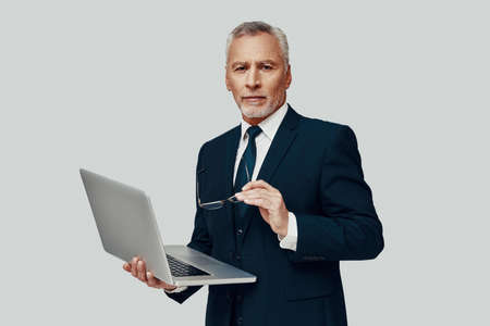 Handsome senior man in full suit using laptop and looking at camera while standing against grey background