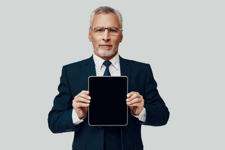 Handsome senior man in full suit pointing copy space on digital tablet and smiling while standing against grey background