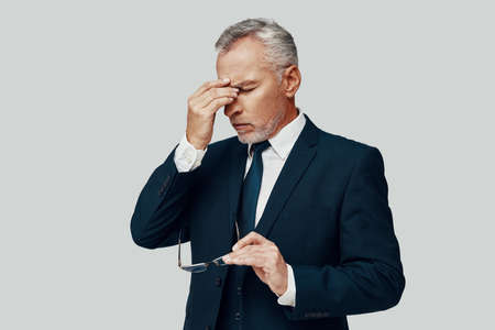 Frustrated senior man in full suit suffering from headache while standing against grey background