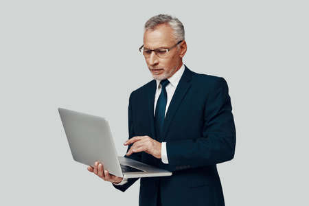 Handsome senior man in full suit using laptop while standing against grey background