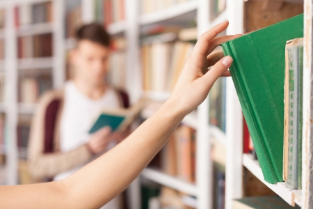 high school students: She has got the book she needs. Someone taking a book from the book shelf while young man reading on the background