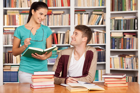 Studying together. Cheerful young man sitting at the desk while beautiful woman standing close to him and holding book photo