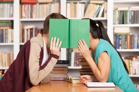 love kiss: Library romance. Young man and woman sitting close to each other at the library desk and hiding their faces behind a book Stock Photo