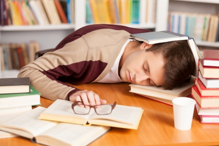 only one man: Sleeping at the library. Tired young man sleeping in the library Stock Photo