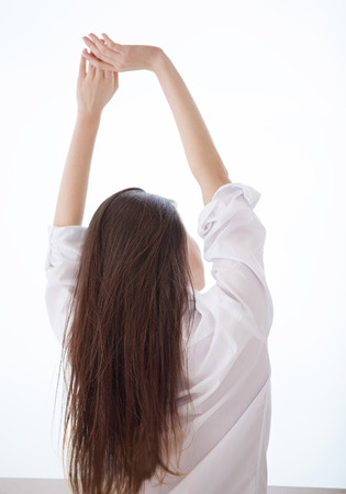 Good morning! Rear view of young woman in shirt stretching and looking through a window photo