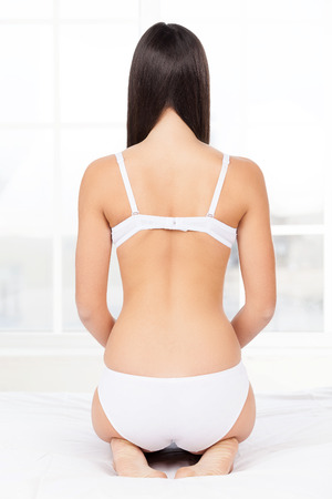 Woman in lingerie. Rear view of young woman in lingerie kneeling on the bed photo