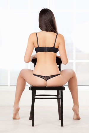 Beauty on the chair. Rear view of woman in black lingerie sitting on the chair  photo