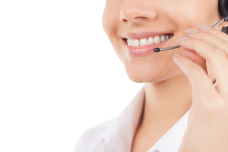 cropped image: Customer service representative. Cropped image of beautiful young woman in headset smiling while isolated on white