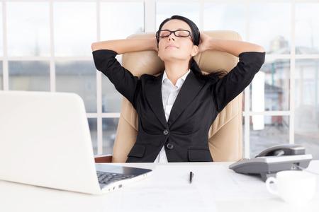 ojos cerrados: Chill tiempo. Alegre mujer de negocios joven sosteniendo la cabeza en las manos y mantener los ojos cerrados, mientras estaba sentado en su lugar de trabajo