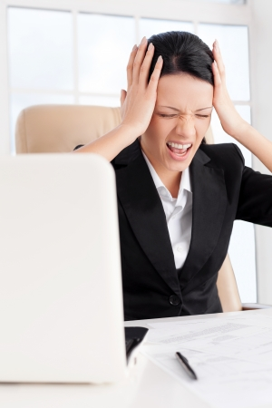 mouth closed: Emotional stress. Young business woman holding head in hands and shouting while sitting at her working place