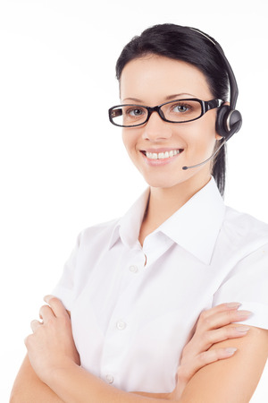Customer service representative. Confident young woman in headset smiling and keeping her arms crossed while standing isolated on white photo