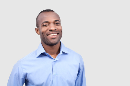 Satisfied man. Cheerful young black man smiling at camera while standing isolated on grey background Stock Photo