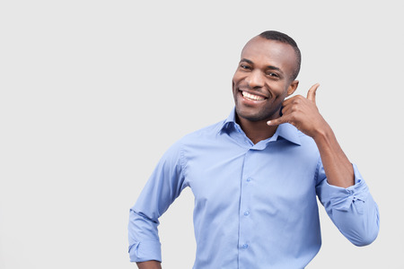 Call me! Handsome young African man showing a call me sign and smiling while standing isolated on grey background Stock Photo